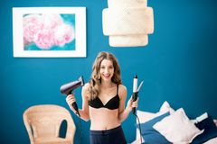 Woman with hairdryer and curler. Portrait of a young happy woman in bra holding hairdryer and electric curler in the bedroom on the blue wall background Royalty Free Stock Photography