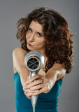 Woman with hairdryer, studio shot Stock Images