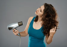 Woman with hairdryer, studio shot Royalty Free Stock Image