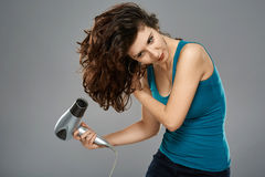 Woman with hairdryer, studio shot Stock Photos