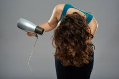 Woman with hairdryer, studio shot Royalty Free Stock Images