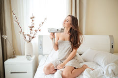 Woman with hairdryier sitting on the bed Stock Photography