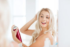 Woman with hairspray styling her hair at bathroom. Beauty, hygiene, hairstyle, morning and people concept - smiling young woman with hairspray styling her hair Stock Images