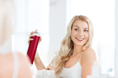 Woman with hairspray styling her hair at bathroom Royalty Free Stock Image