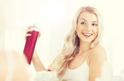 Woman with hairspray styling her hair at bathroom. Beauty, hygiene, hairstyle, morning and people concept - smiling young woman with hairspray styling her hair Stock Image