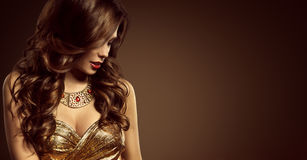 Woman Hairstyle, Beautiful Fashion Model Long Brown Hair Style. Girl in Elegant Golden Dress royalty free stock image
