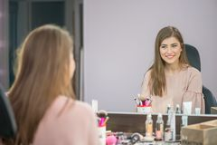 Beautiful woman with hairstyle and makeup looking at the mirror in beauty salon royalty free stock image