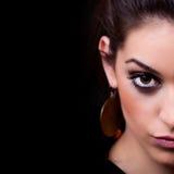 Woman. Half face portrait on black. Background Stock Photos
