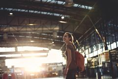 Woman in the hall of the airport terminal with small backpack. Young woman in the hall of the airport terminal with small backpack as a hand luggage. silhouette Stock Photo