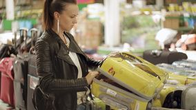 The woman in the store chooses the suitcase for vacation travel. The woman opens the suitcase and sees in the hall of stock video footage