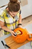 Woman in Halloween decorated kitchen prepare pumpkin for carving Stock Photography
