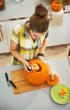 Woman in Halloween decorated kitchen prepare pumpkin for carving. Frightful Treats on the way. Seen from above young woman in the Halloween decorated kitchen stock photography
