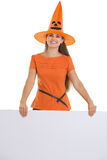 Woman in Halloween hat holding blank billboard Royalty Free Stock Image