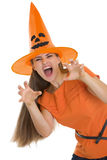 Woman in Halloween hat making scaring pose. Isolated on white Stock Photos