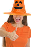 Woman in Halloween hat over eyes showing thumbs up Stock Photo