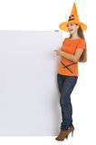 Woman in Halloween hat pointing on blank billboard Royalty Free Stock Photo