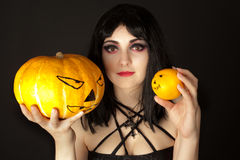 Woman with halloween makeup holding a pumpkin Royalty Free Stock Image