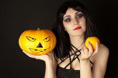 Woman with halloween makeup holding a pumpkin and an orange Stock Photo