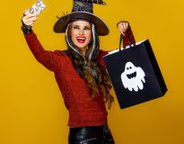 Woman with Halloween shopping bag taking selfie with cellphone. Colorful halloween. smiling modern woman in halloween witch costume on yellow background with royalty free stock image