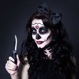 Woman with Halloween skull make up holding knife over black Stock Photos