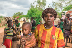 Woman from the Hamar tribe with her child in Ethiopia. TURMI, OMO VALLEY, ETHIOPIA - MAY 5, 2015: Portrait of a woman from the Hamar tribe with her baby in south Stock Image