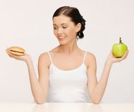 Woman with hamburger and apple Stock Photography