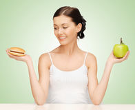 Woman with hamburger and apple Stock Photo