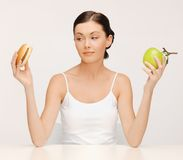 Woman with hamburger and apple Royalty Free Stock Image