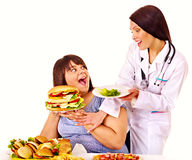 Woman with hamburger and doctor. Stock Images