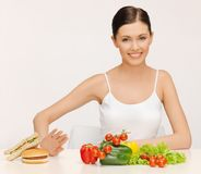 Woman with hamburger and vegetables Stock Photos