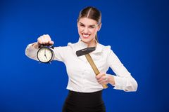 Woman with hammer and alarm clock Stock Images