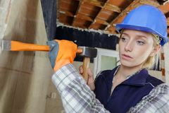 Woman with hammer and chisel working in clients house. Woman stock photography