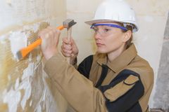 Woman with hammer and chisel working in clients house. Female stock photography