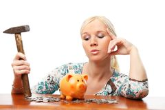 Woman with hammer and piggy bank. Portrait of attractive woman thinking to break a piggy bank. Isolated over white background royalty free stock photo
