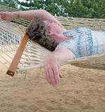 Woman in Hammock. A woman spends some time relaxing in a hammock along a sandy beach Stock Image