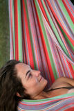 Woman in hammock. A young woman is lying in a couloured hammock Stock Images