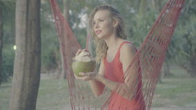 Woman on the hammock at the beach. Pretty blond woman in red smwisuit relaxing in hammock and drinking from coconut isolated on the sandy beach against beautiful stock video footage