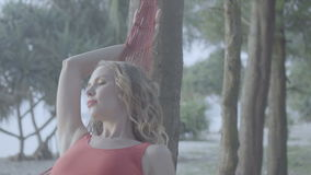 Woman on the hammock at the beach. Pretty blond woman in red smwisuit relaxing in hammock isolated on the sandy beach against beautiful summer tropical stock footage