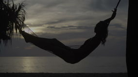 Woman on the hammock at the beach. Silhouette of young woman in smwisuit relaxing in hammock during sunset isolated on the sandy beach against beautiful sea stock video footage