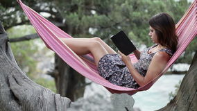 Woman in hammock on e-book stock video footage