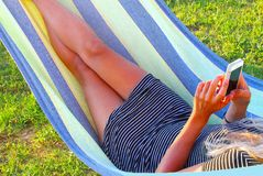 Young woman hammock mobile phone relaxing nature. Woman looks on her mobile phone while relaxing in a hammock in nature Royalty Free Stock Photo
