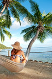 Woman on hammock in tropical island palm trees. Beautiful tropical vacation in the warm sunny Seychelle island oceans and palm trees Royalty Free Stock Image