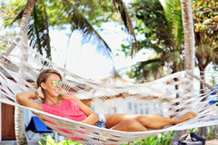 Woman in the hammock under the palms on the tropical beach Stock Photo