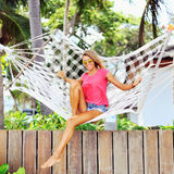 Woman in the hammock under the palms on the tropical beach Stock Photography