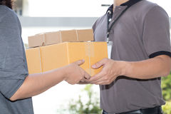 Woman hand accepting a delivery of boxes from deliveryman Stock Photos