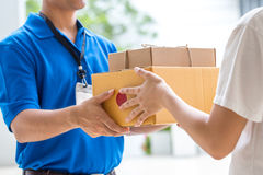 Woman hand accepting a delivery of boxes from deliveryman Stock Images