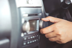 Woman hand adjusting the sound volume of car radio. While driving a car in vintage color tone Stock Photography