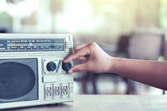 Woman hand adjusting the sound volume on retro radio cassette. Stereo  in vintage color tone Stock Photo