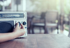 Woman hand adjusting the sound volume on retro radio cassette. Stereo  in vintage color tone Stock Images