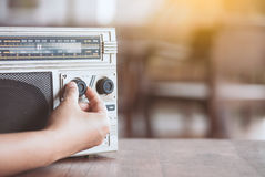Woman hand adjusting the sound volume on retro radio cassette. Stereo  in vintage color tone Royalty Free Stock Photography